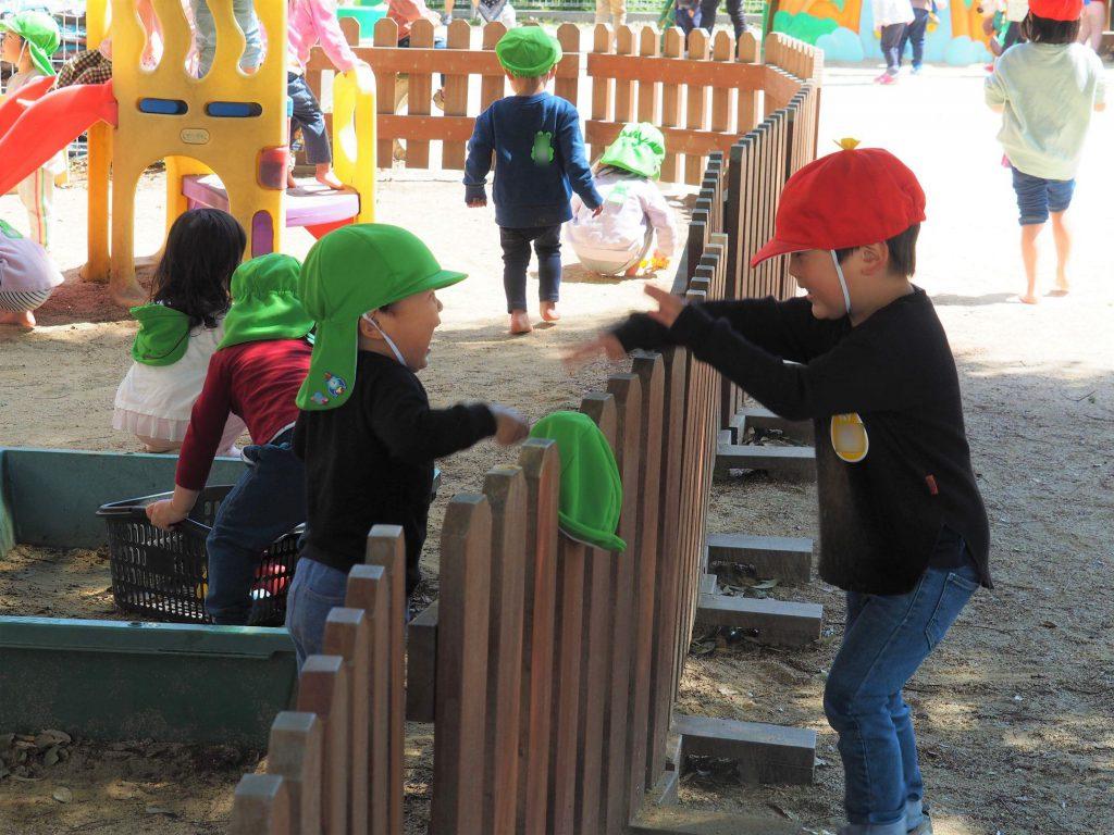 自然と乳児園庭に遊びに来た、幼児組のお兄さん、お姉さん。異年齢交流で思いやりのこころを持っていきます。